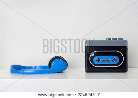 Retro cassette player and headphones on the white shelf