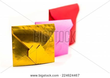 valentine's day concept. pile of colorful origami paper envelopes isolated on white. pink, red and gold envelopes lay on white background