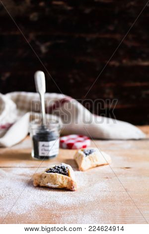 Homemade traditional jewish cookies Hamantaschen with dried plum and poppy seed with icing sugar for jewish holiday Purim, selective focus
