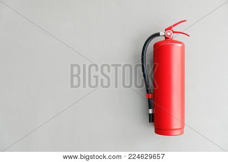 Red Fire Extinguisher On The Gray Wall