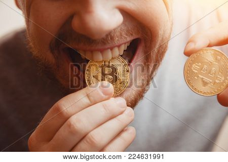 Bitcoin. Man bites a gold coin with his teeth