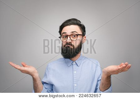 Young bearded man in bewilderment shrugging his shoulders and looking at camera with confusion.
