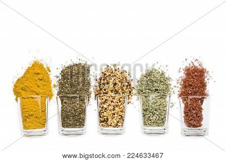 glass jars with various spices on white background with copy space