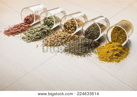 glass jars with various spices on wooden table