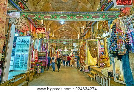 SHIRAZ, IRAN - OCTOBER 12, 2017: The  brick alley of historic Vakil Bazaar with stores of textile department, offering curtains, tulle, furniture and fabrics, Shiraz, Iran, on October 12 in Shiraz.