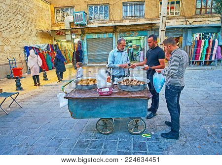 SHIRAZ, IRAN - OCTOBER 12, 2017: The street vendor in Bazar-e No with old wooden cart sales the popular local dish - spicy beans and chickpeas, on October 12 in Shiraz.