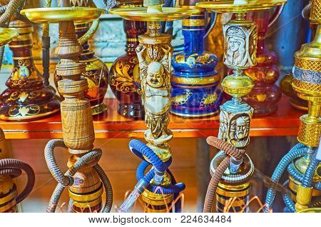 The shisha water pipes are decorated with carved ivory, depicting Buddha and antique portraits, the market stall in Shiraz, Iran. poster