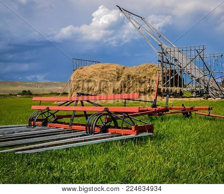 Haying equipment powered by horses used on the northern plains in early 1900s.  Shown here a buck rake, foreground, and hay stacker known as a beaver slike.