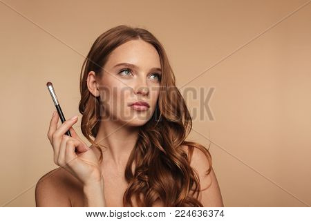 Beauty portrait of pensive ginger woman with long hair looking up while holding cosmetics brush over cream background