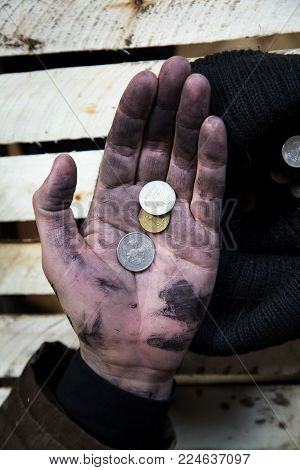 Modern beggar Russia 2000. A vagabond alcoholic in his dirty hand holds Russian coins.