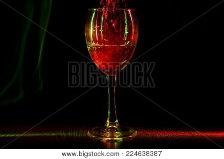 A goblet in night club. Restless wine in a glass. The light effect. On a black background. Close-up.