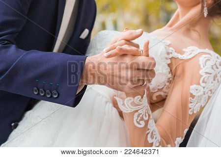The bridegroom holds the bride's hand, the moment of the dance