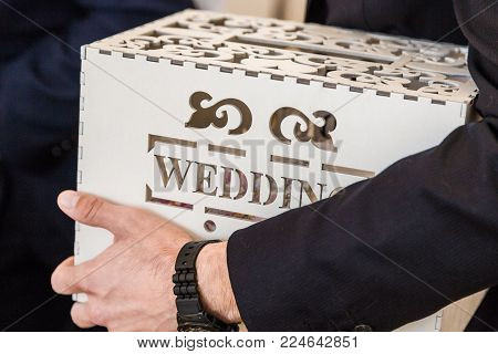 Man holds in his hand a wedding box with a wedding inscription for wedding greetings and gifts