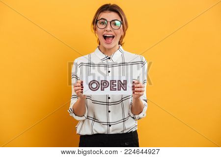 Portrait of joyous woman with auburn hair holding open sign and looking at camera isolated over yellow background poster