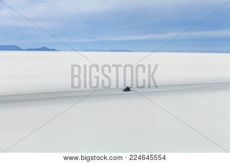 off-road vehicle driving on Salar de Uyuni. Stock photo