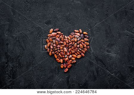 Roasted cocoa beans on black background top view copy space. Raw material for cocoa powder. African or Latin American product.