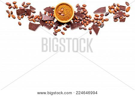 Chocolate and cacao concept. Cocoa powder in bowl near cocoa beans and broken chocolate on white background top view.