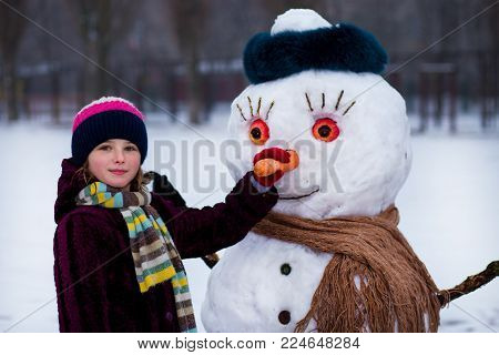 A Small Cheerful Girl Holds A Big Carrot, The Nose Of A Big Snowman. A Cute Little Girl Has Fun In W