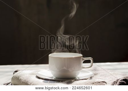 Hot black coffee in white ceramic cup and saucer on cozy wool scarf with nice steam warm sunlight in morning and copy space for text, logo or wording insertion over dark grey background, hot beverage