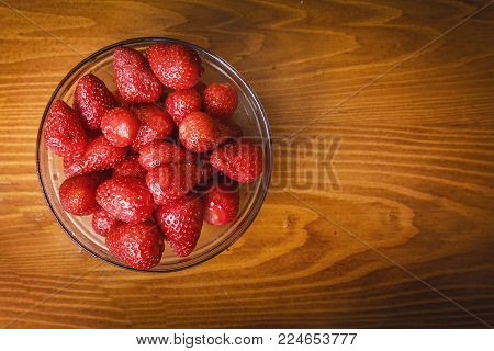 Glass bowl full of pealed and clean fresh strawberries on a wooden surface