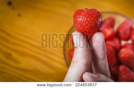 Two fingers holding a strawberry against wooden yellow background, no petals, pealed