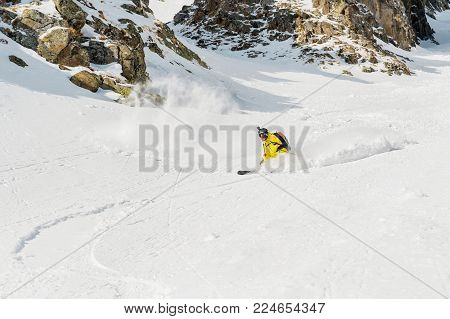 A male skier freerider with a beard descends the backcountry at high speed from the slope leaving a trail of snow powder behind him against the background of epic rocks. The concept of freeriding culture and backcountry destinations in extreme skiing