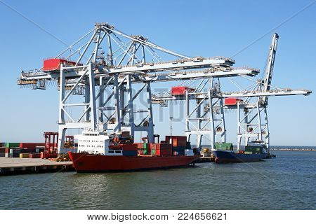 Huge container handling gantry cranes at a container terminal. Loading cargo ship. Blue sky background