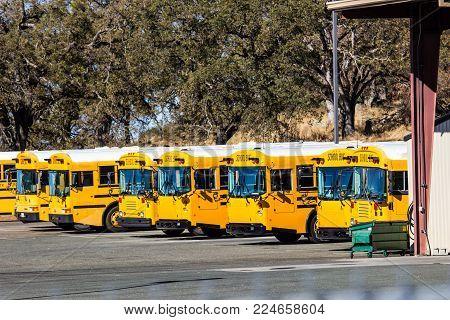 Row Of School Buses In Maintenance Yard