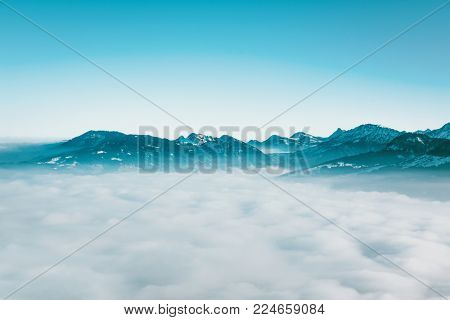 Minimalist cloudy atmospheric landscape with distant mountain peaks visible in the background above a layer of white cloud