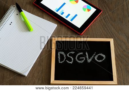 Plate with the inscription DSGVO (Datenschutzgrundverordnung) in English GDPR (General Data Protection Regulation) with a tablet and block for the introduction of the DSGVO in the EU