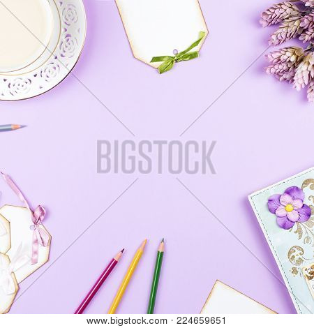 Scrapbook background with decoration, tea cup, flowers on purple background, copy space. Top view