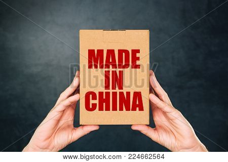 Man holding cardboard box product package with Made in China label imprint for merchandise goods imported from East Asia