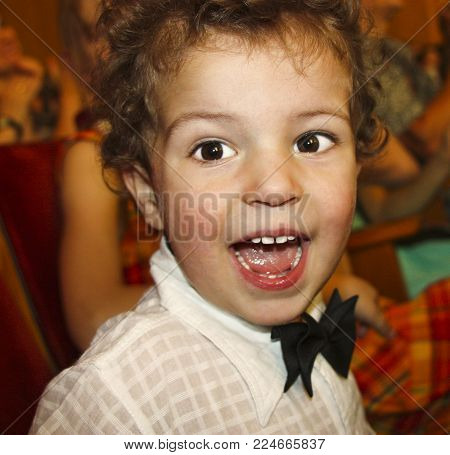 Portrait of a happy little boy in a white shirt and a bow tie. A gentleman in the auditorium.