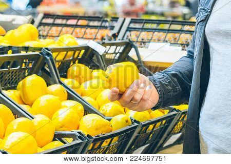 young man choose lemon in the store