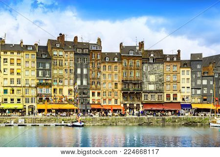 HONFLEUR, NORMANDY / FRANCE - MAY 23, 2013: The picturesque old port of Honfleur, founded by vikings, restaurants, shops and traditional buildings.
