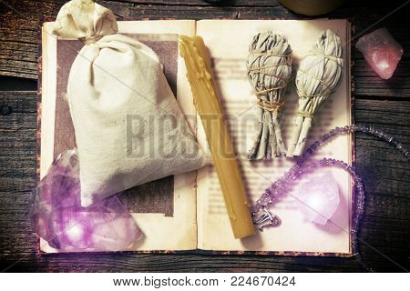 Natural gemstones, white sage, candle, sack on a book on wooden board, witchcraft tools