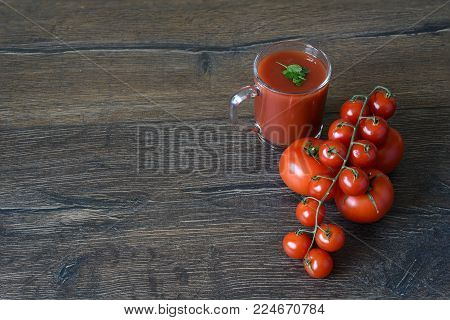 Tomato juice in glass and fresh tomatoes on wooden table