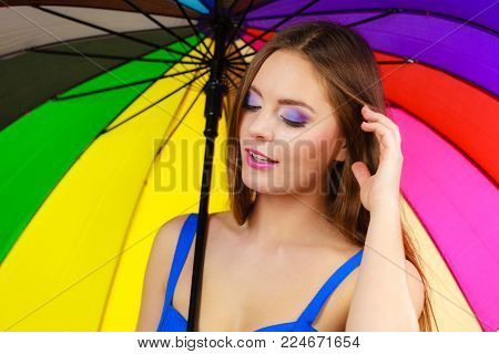 Woman fashionable summer girl standing under colorful rainbow umbrella, close up. Attractive female long hair model. Forecasting and weather season concept