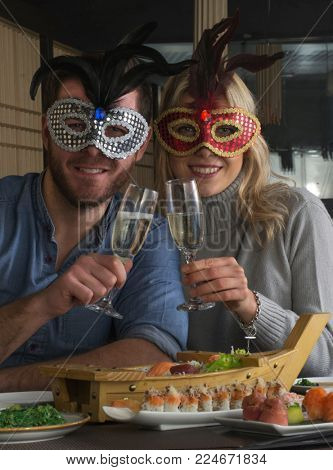 Carnival young couple sharing drinking champagne at sushi restaurant.