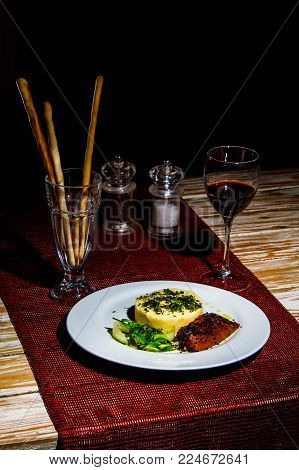 Fresh tasty Omelet with Salmon, sesam seeds, salad and bread sticks near wine glass, salt anr pepper on the wooden table with rustic red tablecloth. Still life, Dark theme.