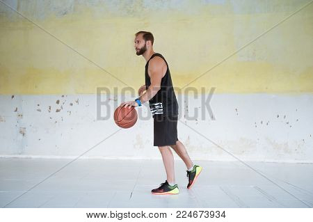 Young man basketball player with ball in hands is prepearing to play.