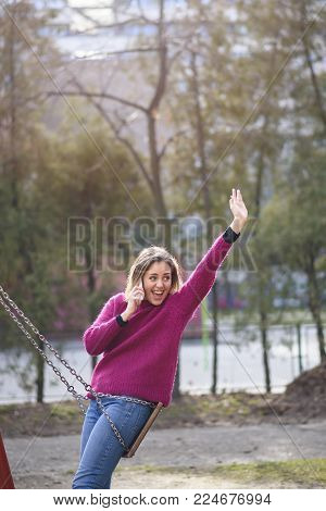 Sweet young woman saying hello to a an acquaintance while talking on her cell phone, park and outdoors scene
