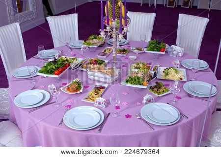 The elegant dinner table. Wedding table decorated with candles, served with cutlery and crockery and covered with a tablecloth . Pink tablecloth . White chairs . White wedding table. A table decorated with balloons.