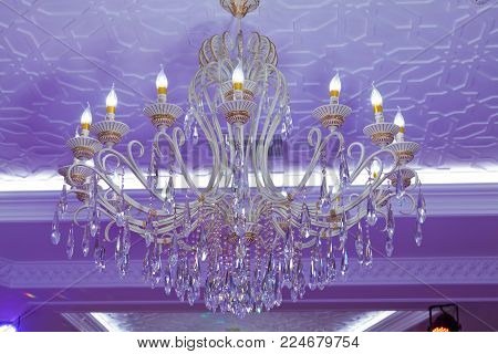 Horizontally framed shot . Stylish antique chandelier lit in violet light. beautiful crystal chandelier for decoration . Pink background .