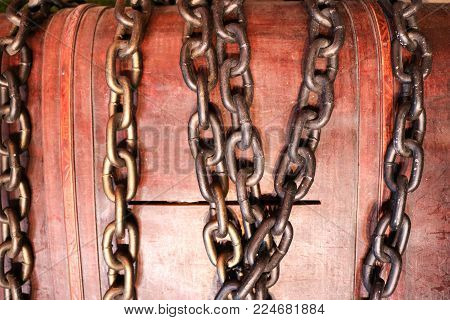 A large, brown, wooden casket, a piggy bank, a chest locked with a lock of iron strong chains.