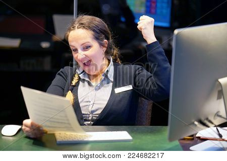 Close-up of a woman-reception hotel worker. Happy lady, enjoying the good news in writing. An euphoric girl is happy after reading good news in a written letter, approving a loan, raising her job.
