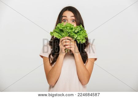 Portrait of a surprised young asian woman holding lettuce at her face isolated over white background