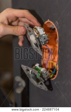 Skilled worker installs circuits on a wall - close-up