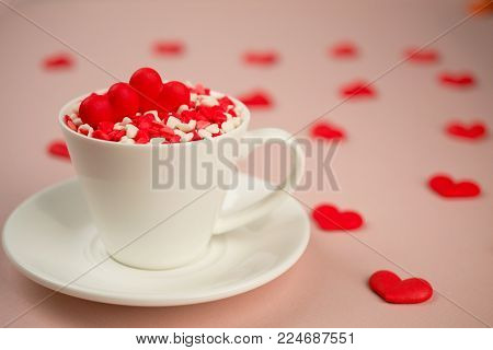 Red sweet  sugar candy hearts in a  coffee cup. Love and Valentine's day concept. Festive background