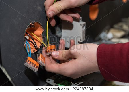 Skilled worker installs electrical circuits on a wall - close-up